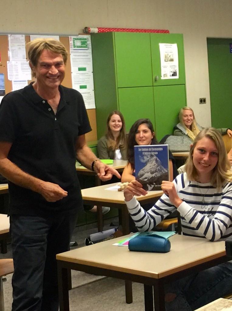 Christophe Carron avec une élève qui tient dans ses mains le livre du Père Rougier.